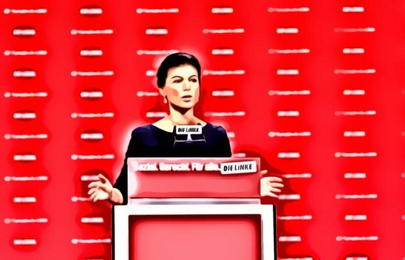 Sahra Wagenknecht vor einer Roten Wand an einem Rednerpult. Sie gründete Aufstehen 2018.